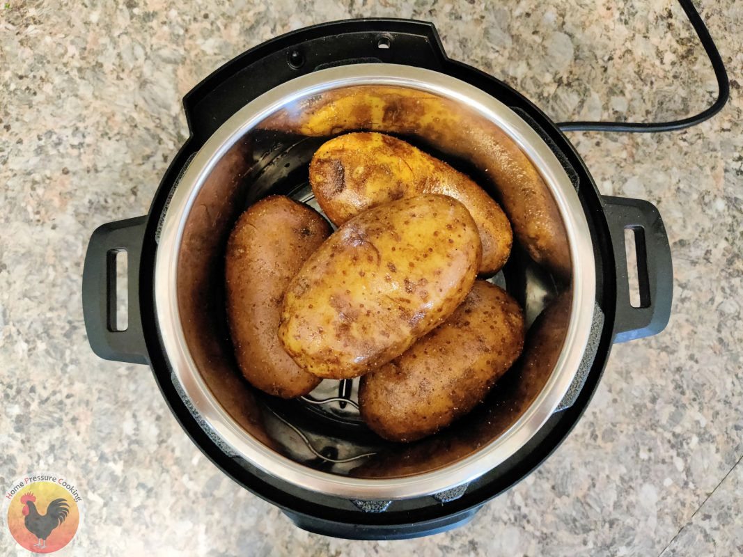 Four potatoes being placed in the bottom of a Instant Pot as they are preparing to cook.