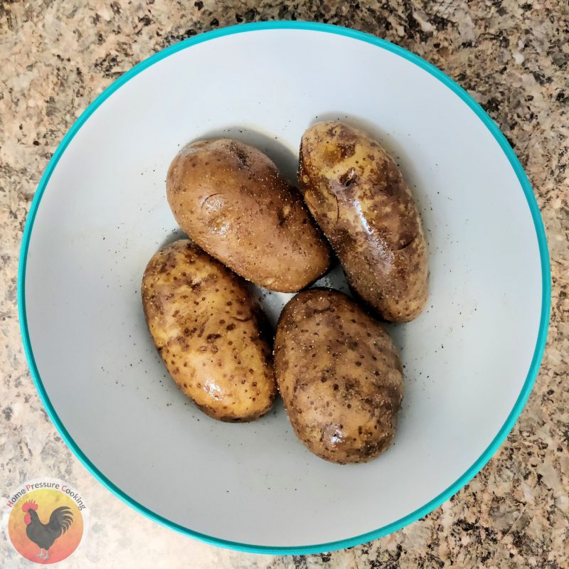 Four potatoes in a large mixing bowl that are coated in olive oil and seasoned with salt and pepper.